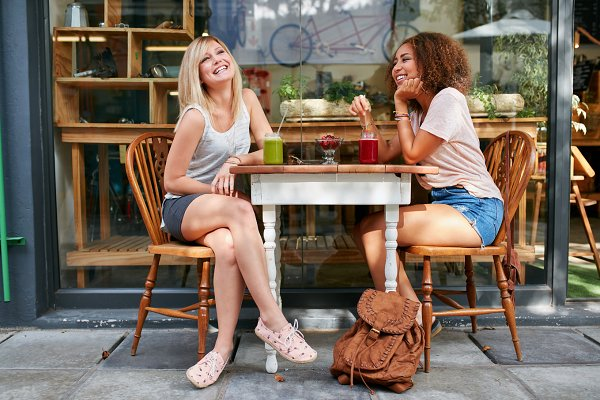 Female friends hanging out at sidew…
