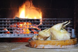 Whole chiken near the fireplace.