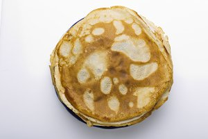 Pancakes on a plate on a white backg