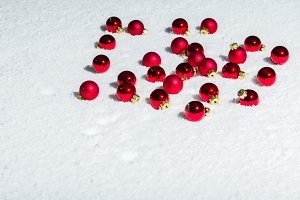 Red Christmas ornaments on snow