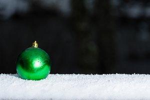 Green ornament in snow