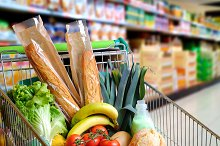 Shopping cart full of food in supermarket aisle elevated view.jpg