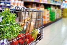 Shopping cart full of food in supermarket aisle side tilt.jpg
