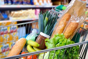 Shopping cart full of food in the supermarket side view.jpg