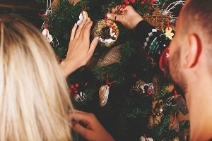 Young couple decorating tree
