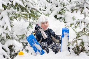 little girl in skiing sits on snow