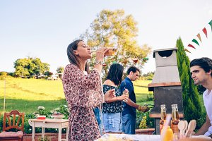 Woman drinking beer in a barbecue