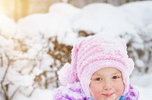 Cheerful little girl snow playing