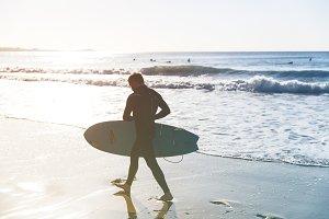 Surfer on beach on sunny day