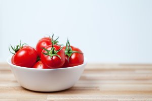 Fresh tomatoes in a bowl on wooden t