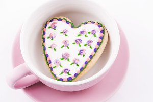 Heart-shaped biscuit into a cup.