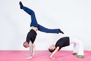 Two acrobats dancing capoeira
