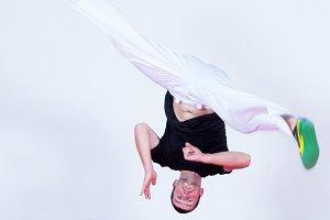 Young man jumping, dancing capoeira