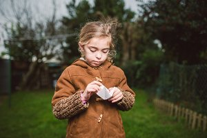 girl playing with a piece of paper