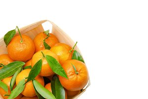 Tangerines with leaves in wooden box