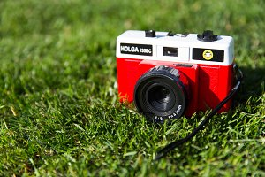 Red retro camera on grass