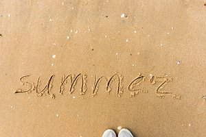 Summer written on a beach sand