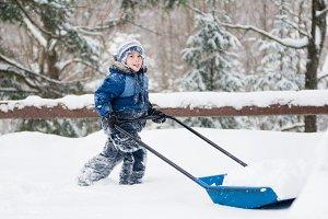 boy shoveling snow in a blizzard