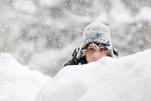 Boy peeking over a snowbank
