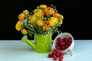 flowers with a cup of raspberries