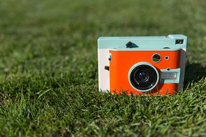 Retro orange camera in grass
