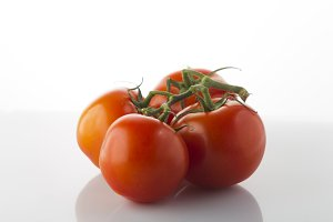 Red tomatoes on a green branch on a