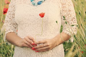 Bride with red poppy in hand.