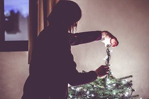 Woman decorating a christmas tree.