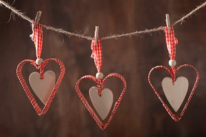 red hearts hanging over wooden backg