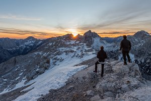 Male hikers watching mountain sunset