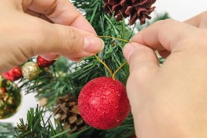 Woman puts a ball in the xmas tree