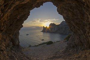 Sun setting behind coastal cliffs