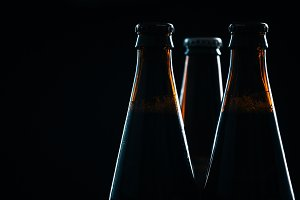 three bottle of dark  beer