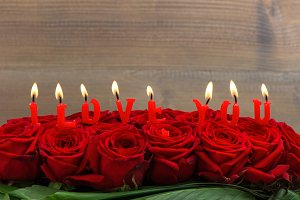 Red roses and burning candles. LOVE