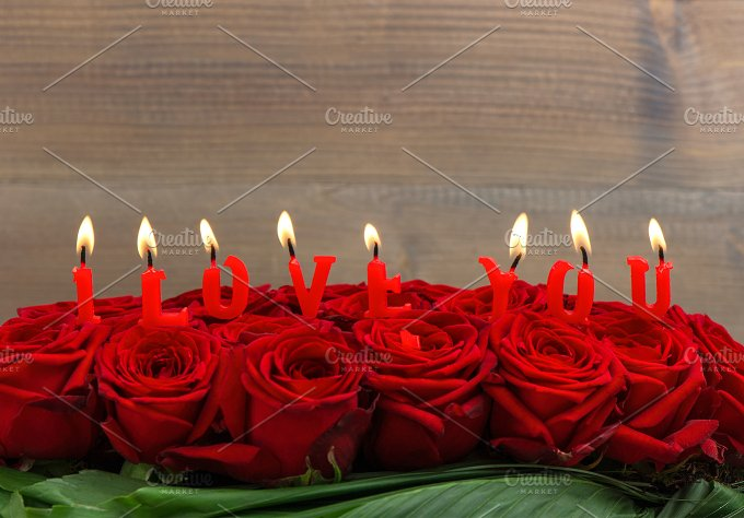 Red roses and burning candles. LOVE - Holidays
