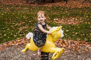 Toddler girl riding playground pony