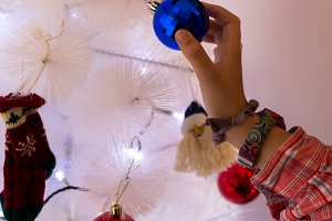 Girl placing Christmas ornaments