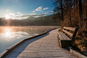 Bench by the lake at sunrise