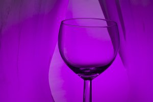 Wine glass on an abstract colored bo
