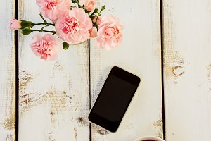 Smartphone, cup of coffee and flower
