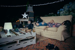Young drunk friends sleeping in sofa