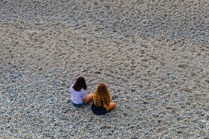 Two girls sitting on the beach.jpg