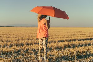 child with umbrella in the field