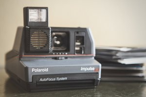 Polaroid Camera and a Stack of Film