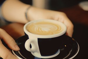 A woman holding a cup of hot latte