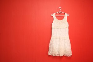 Hanger white dress on the red wall