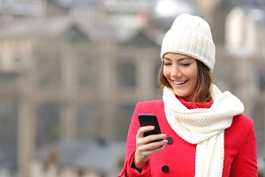 Girl texting in a mobile phone in winter.jpg