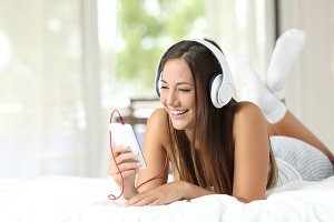 Girl listening to music from a smartphone at home.jpg