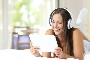 Girl listening to music from a tablet at home.jpg