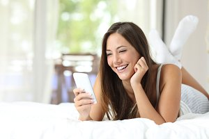 Girl using a mobile phone on the bed at home.jpg